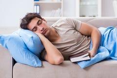 Il giovane uomo dello studente che prepara per gli esami dell'istituto universitario a letto con il libro Fotografia Stock Libera da Diritti