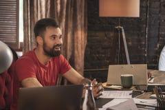Il giovane uomo di affari che si siede dentro inizia sullo studio scuro accogliente alla tavola di legno Immagini Stock Libere da Diritti