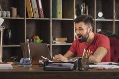 Il giovane uomo di affari che si siede dietro lo scrittorio e vede le notizie fresche sul computer portatile Immagini Stock Libere da Diritti