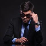 Il giovane uomo di affari esamina i suoi occhiali da sole Immagine Stock
