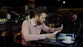 Il giovane uomo di affari ha girato il ribaltamento che lavora in una barra stock footage