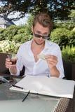 Il giovane uomo di affari sta contando i dollari nel giardino e sta avendo immagini stock libere da diritti