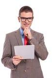 Il giovane uomo di affari tiene la compressa e sorride con la mano sul mento Fotografie Stock
