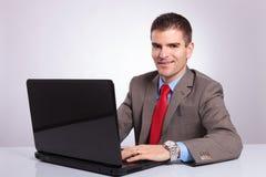 Il giovane uomo di affari vi esamina mentre lavora al computer portatile immagini stock