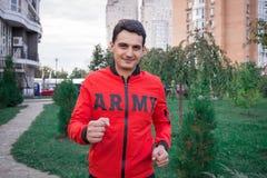 Il giovane uomo di forma fisica funziona durante il suo allenamento di addestramento Fotografie Stock Libere da Diritti