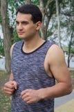 Il giovane uomo di forma fisica funziona durante il suo allenamento di addestramento in parco Fotografia Stock Libera da Diritti