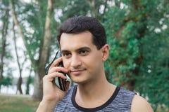 Il giovane uomo di forma fisica parla dal telefono cellulare durante l'allenamento di addestramento Fotografie Stock Libere da Diritti