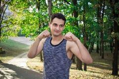 Il giovane uomo di forma fisica prepara per l'allenamento d'inscatolamento in parco Fotografie Stock