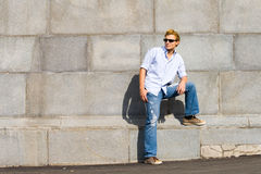 Il giovane uomo di modo si leva in piedi contro la parete immagini stock libere da diritti