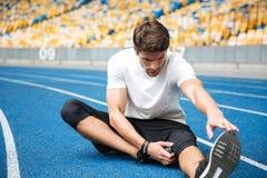 Il giovane uomo di sport allo stadio fa l'allungamento degli esercizi Immagine Stock Libera da Diritti