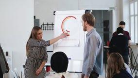 Il giovane uomo e la donna intelligenti di affari che presentano le vendite proiettano al seminario dell'ufficio, discutendo il l video d archivio