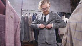 Il giovane uomo elegante sceglie il vestito classico in deposito archivi video