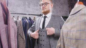 Il giovane uomo elegante sceglie il vestito classico in deposito video d archivio