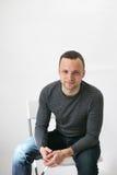 Il giovane uomo europeo sta sedendosi sulla sedia bianca Fotografia Stock Libera da Diritti