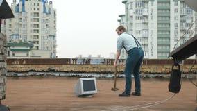 Il giovane uomo forte fracassa il monitor con una mazza sul tetto Martello, pipistrello, violenza, odio, anarchia archivi video