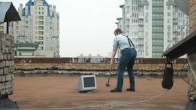 Il giovane uomo forte fracassa il monitor con una mazza sul tetto Martello, pipistrello, violenza, odio, anarchia stock footage