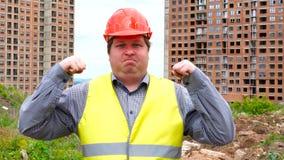 Il giovane uomo grasso caucasico sul fondo del cantiere, mostra il potere ed il muscolo, garantisce l'affidabilità ed i risultati stock footage