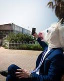 Il giovane uomo insolito nella maschera della testa di cavallo ed in vestito elegante fa una foto dal telefono immagini stock