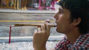 Il giovane uomo meditativo gioca il tubo in tempo piovoso Movimento lento 1920x1080 video d archivio
