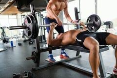 Il giovane uomo muscolare bello che fa la stampa di banco ed ottiene l'aiuto fotografia stock