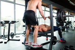 Il giovane uomo muscolare bello che fa la stampa di banco ed ottiene l'aiuto immagini stock