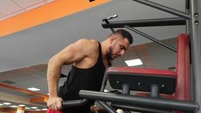 Il giovane uomo muscolare durante l'addestramento nella palestra esegue i piegamenti sulle braccia sulle barre