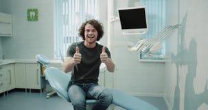 Il giovane uomo paziente in uno studio del dentista che si siede sulla sedia del dentista e che aspetta il suo controllo orale ha video d archivio