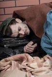 Il giovane uomo senza tetto è lapidato fotografia stock