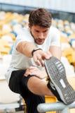 Il giovane uomo serio di sport allo stadio fa l'allungamento degli esercizi Fotografia Stock Libera da Diritti