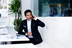 Il giovane uomo sicuro che parla sullo Smart Phone durante il lavoro irrompe la caffetteria moderna Fotografie Stock Libere da Diritti