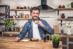 Il giovane uomo sorridente bello sta bevendo il suo caffè di mattina con il croissant e un succo di mele alla cucina fotografie stock libere da diritti