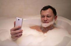Il giovane uomo sorridente si siede il bagno fa la barba prende il selfie fotografia stock