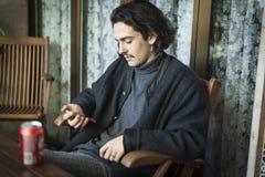 Il giovane uomo spagnolo gode di una birra che si siede su un terrazzo e che per mezzo dello smartphone immagini stock libere da diritti