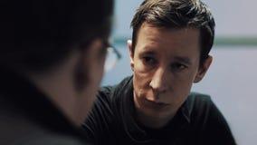 Il giovane uomo subtile triste ascolta il suo capo o padre in vetri video d archivio
