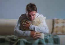Il giovane uomo triste e disperato a casa che si siede alla depressione ed allo sforzo di sofferenza del sofà dello strato del cu Fotografie Stock Libere da Diritti