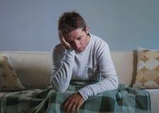 Il giovane uomo triste e disperato a casa che si siede alla depressione ed allo sforzo di sofferenza dello strato del sofà si è p Immagini Stock