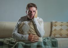 Il giovane uomo triste e disperato a casa che si siede alla depressione ed allo sforzo di sofferenza dello strato del sofà si è p Immagine Stock