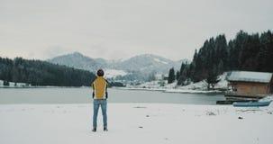 Il giovane uomo turistico ammira la vista stupefacente del lago e montagna verso la metà dell'inverno con la foresta nevosa, è video d archivio