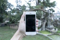 Il giovane utilizza il suo telefono cellulare per prendere le immagini delle sue memorie immagini stock libere da diritti