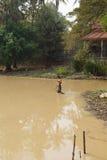 Il giovane utilizza un rastrello per pescare il pesce Immagine Stock