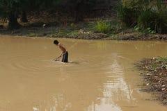 Il giovane utilizza un rastrello per pescare il pesce Fotografie Stock