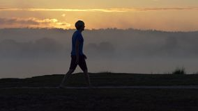 Il giovane va lungo una banca del lago al tramonto nel slo-Mo stock footage