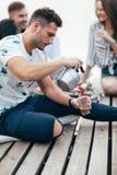 Il giovane versa il tè nella tazza sul picnic fotografia stock