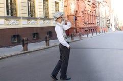 Il giovane in vestiti alla moda passeggia sulla via della città Fotografia Stock