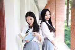 Il giovane vestito grazioso cinese asiatico dello studente di usura delle ragazze a scuola gode del libro colto tempo libero nel  Immagini Stock