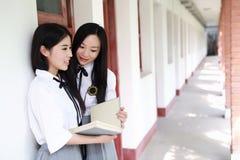 Il giovane vestito grazioso cinese asiatico dello studente di usura delle ragazze a scuola gode del libro colto tempo libero nel  Fotografie Stock