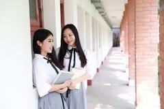 Il giovane vestito grazioso cinese asiatico dello studente di usura delle ragazze a scuola gode del libro colto tempo libero nel  Immagine Stock