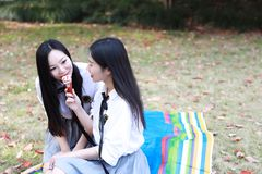 Il giovane vestito grazioso cinese asiatico dello studente di usura delle ragazze a scuola mangia il gelato nel giardino della na Fotografia Stock