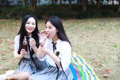 Il giovane vestito grazioso cinese asiatico dello studente di usura delle ragazze a scuola mangia l'acqua della cola dell'arancia Immagini Stock