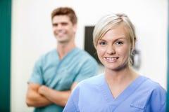 Il giovane veterinario femminile dentro sfrega sorridere Fotografie Stock Libere da Diritti